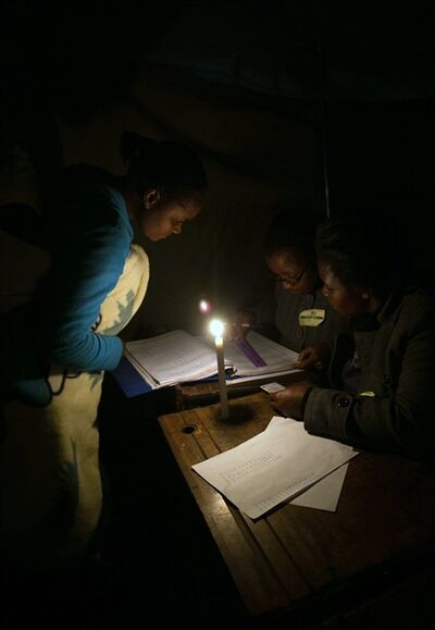 In this Wednesday, July 31, 2013 photo, voting takes place by candlelight in Harare. President Robert Mugabe's ZANU PF party said Thursday, Aug. 1, 2013, that it has withdrawn an unauthorized message on its Twitter feed claiming a resounding victory in the country's national elections. (AP Photo/Clarissa Sosin) SOUTH AFRICA OUT