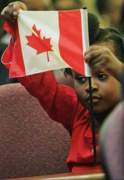 Divine Mugugu, 4, waves a flag after reaffirming the oath of citizenship at the Union Station Citizenship Court on last year.