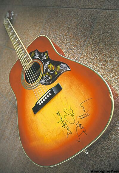 Someone will win this guitar autographed by the members of Doc Walker.