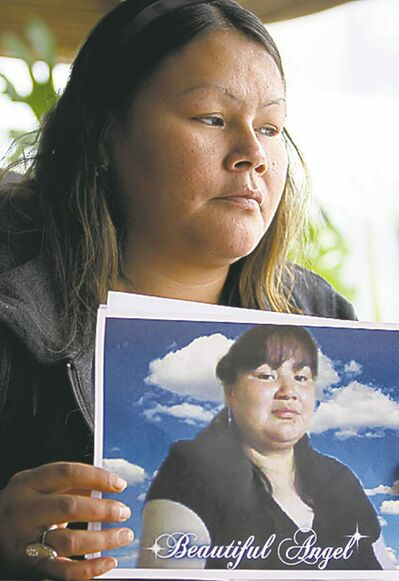 Corina Okemow holds a picture of her younger sister Tracy at a press conference Thursday afternoon.