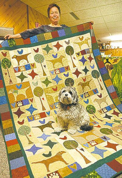 KEN GIGLIOTTI / WINNIPEG FREE PRESSRita Wasney of Manitoba Prairie Quilters displays a quilt to be auctioned, with help from her dog Wilton.