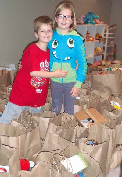 Bailee Gill, 7 and her brother Josh, 5, show off the flood of Share Bags brought in by their school mates in support of a Winnipeg food bank.