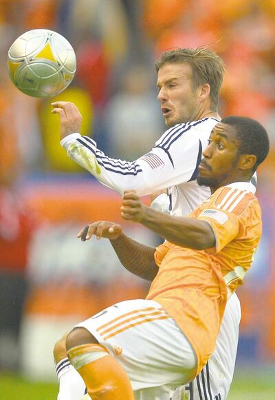 Galaxy midfielder David Beckham (left) and Houston Dynamo midfielder Corey Ashe contest possession.