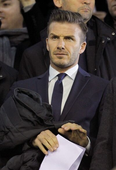 Newly signed Paris Saint-Germain player David Beckham stands in the tribunes prior to a Champions League round of 16 first leg soccer match between Valencia and Paris Saint-Germain at the Mestalla stadium in Valencia, Spain, Tuesday, Feb. 12, 2013. (AP Photo/Fernando Hernandez)