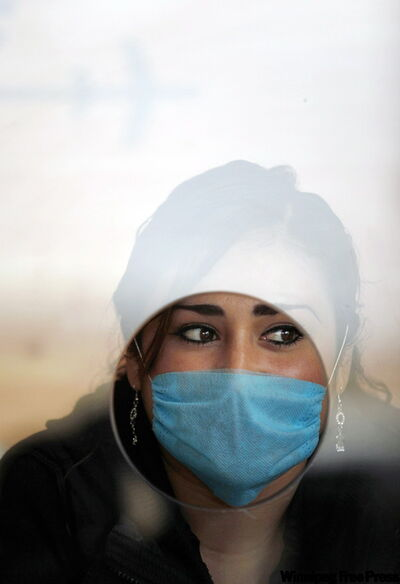 Mexican worker protects herself from swine flu. A city lab discovered the outbreak.