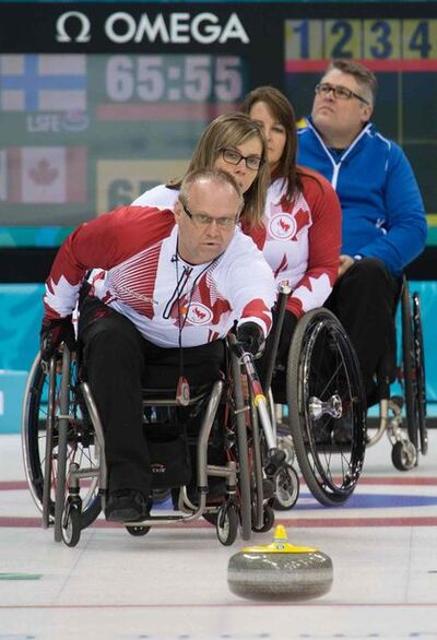 Dennis Thiessen, of Sanford, sends a rock down the ice, watched by teammates Sonja Gaudet and Ina Forrest during the Canadian team's game against  Finland at the 2014 Sochi Paralympic Winter Games.
