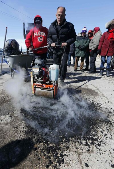 Pellet Patch sales rep Saverio Marra uses a roller to smooth hot mixture into a pothole. The City of Winnipeg currently uses a cold-mix patching material during the late winter and early spring to fill potholes.