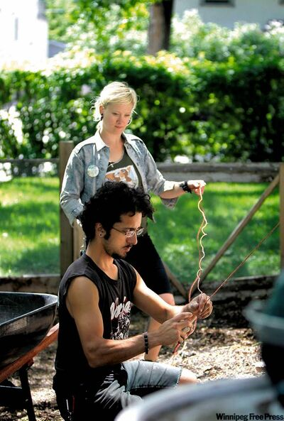 Paolo Riva and Kim Bialkoski tie up a trellis for cucumber plants to climb in a customer's garden.