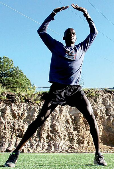In a Wednesday, Aug. 1, 2012, photo, Guor Marial, 28, does jumping jacks on a soccer field in Flagstaff, Ariz. The Sudanese refugee learned just weeks ago that he could compete in the men's marathon at the Olympics as an independent athlete. (AP Photo/Felicia Fonseca)