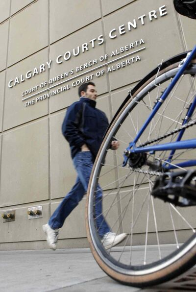 A pedestrian runs along the sidewalk in front of the Calgary Courts Centre where Justice Robin Camp presided over the case of a sexual assault involving a 19-year-old homeless woman.