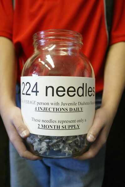 A boy holds a jar illustrating the needles that a child with juvenile diabetes needs to use over two months.