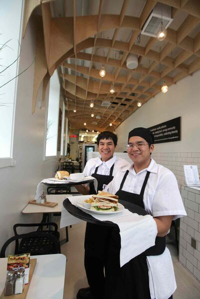Sheldon Lachose (front) and his twin brother, Eldon, serve food at the new Lunch Bell restaurant in the city's gritty core.