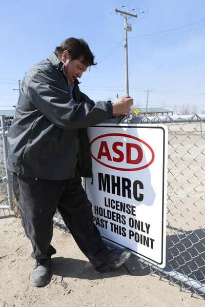Assiniboia Downs employee Mel Nault attaches a sign to the backstretch area as a result of MHRC security concerns.