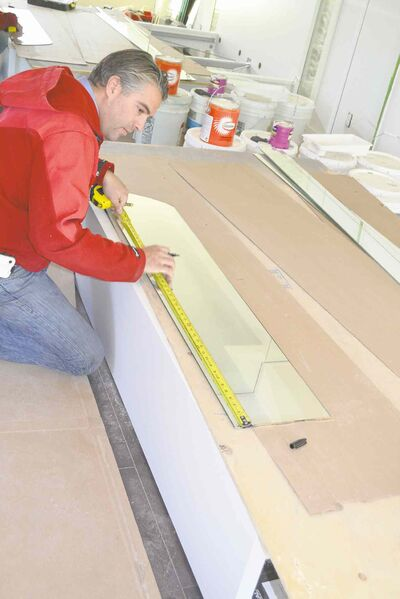 Steve prepares to cut a piece of mirror to be used as a riser on the entranceway staircase