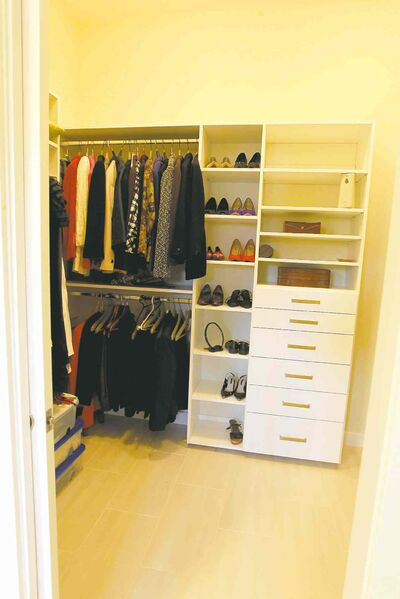 A huge walk-in closet features a tile floor and built-in storage.