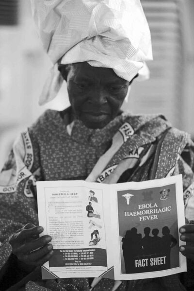 The Associated Press filesA woman reads a fact sheet for the Ebola virus during an awareness campaign in Lagos, Nigeria, Aug. 15.