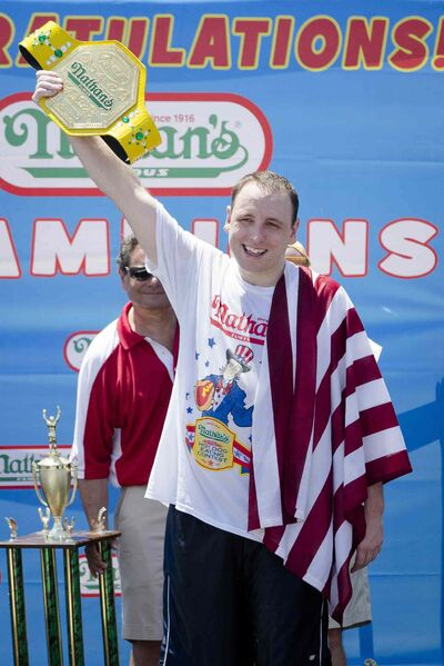 Joey Chestnut holds the Mustard Yellow belt as he celebrates winning the Nathan's Famous Fourth of July International Hot Dog Eating contest with a total of 69 hot dogs and buns in 2013 at Coney Island in New York.