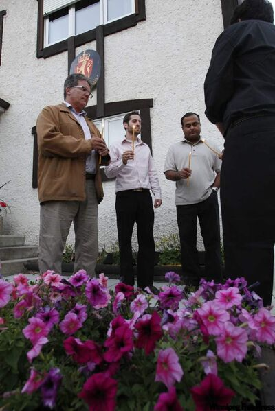 A group of Liberals sing Amazing Grace as part of a vigil for Norway in front of the Norwegian Consulate in Fort Richmond Sunday.