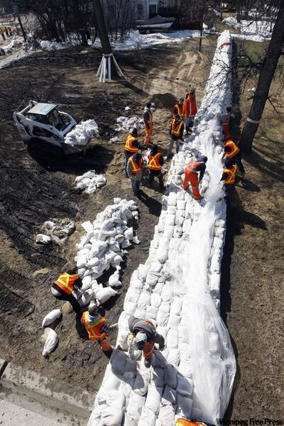 City workers sandbagging along the Red River at Kingston Row earlier this month.