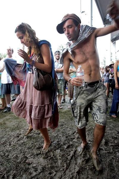 FILE - Georgia Ainsworth, left, of Toronto, and Lee Piazza, right, Ottawa, dance in the mud during an Iron and Wine concert at the Bonnaroo Music and Art Festival in Manchester, Tennessee, on June 14, 2008. Heavy rains from Hurricane Ida forced Bonnaroo to cancel as the organizer said the waterlogged festival grounds were unsafe for driving or camping.  On social media, the festival said on Tuesday, August 31, 2021 that huge rainfall over the past 24 hours, the remnants of Ida's powerful winds and rain, saturated the trails and camping areas.  (AP Photo / Mark Humphrey, file)