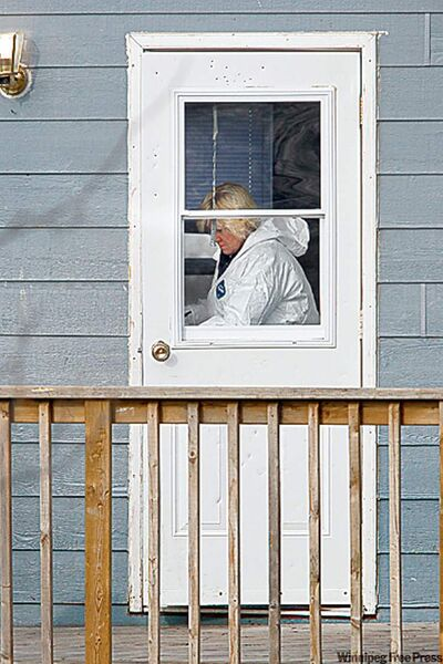 A forensics officer gathers evidence inside the home Friday.