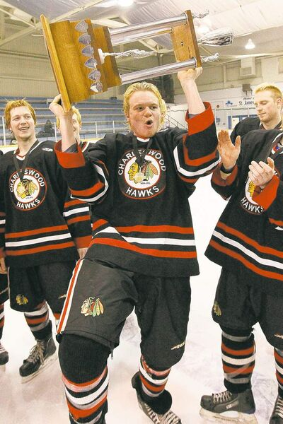The Hawks' Jesse Toth lifts the Jack McKenzie Trophy after taking the league final Friday night.
