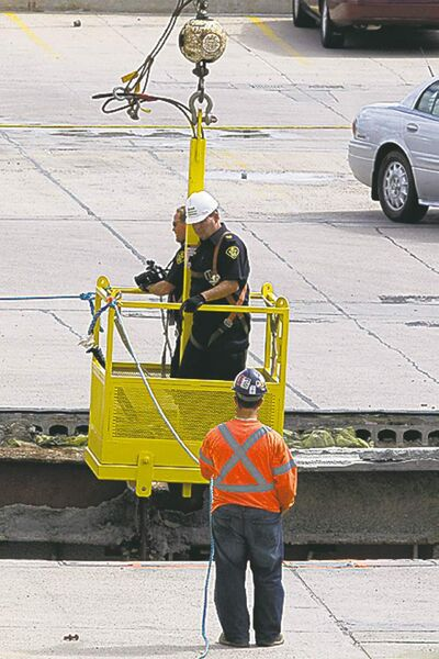 Chris Young / THE CANADIAN PRESS Police and rescuers work at the scene of the roof collapse Monday.