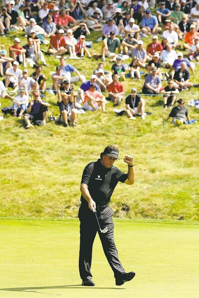 Phil Mickelson celebrates after his birdie putt on the ninth hole Thursday.