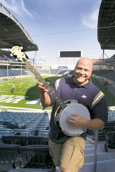 Troy Westwood poses with a banjo at Investors Group Field.