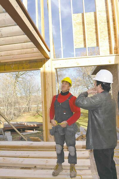 Larwyn and his main framer, Gerald, discuss how to cover a main beam with drywall.