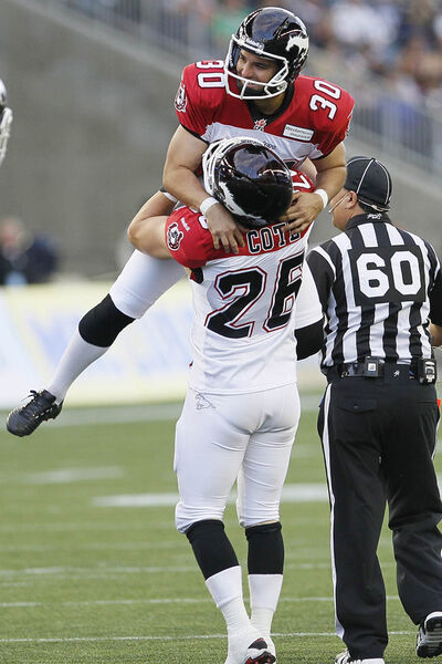 Calgary Stampeders' Rene Paredes (30) and Rob Cote (26)celebrate Paredes' record making field goal kick during the first half of their CFL game against the Winnipeg Blue Bombers at Investors Group Field in Winnipeg Friday, July 26, 2013.