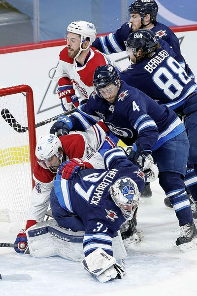 Winnipeg Jets goaltender Connor Hellebuyck (37) dives on the rebound as Montreal Canadiens' Phillip Danault (24) crashes into him and Jets' Neal Pionk (4) defends during the second period. (John Woods / The Canadian Press)