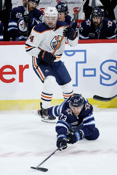 Winnipeg Jets' Trevor Lewis (23) makes the pass after getting checked by Edmonton Oilers' Devin Shore (14) during the first period. (John Woods / The Canadian Press)