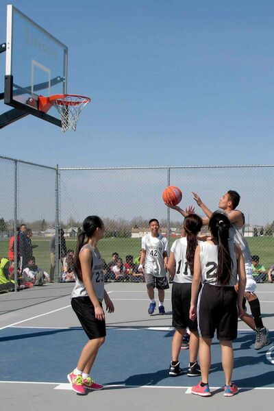 École Stanley Knowles students play basketball on the school's new outdoor court.