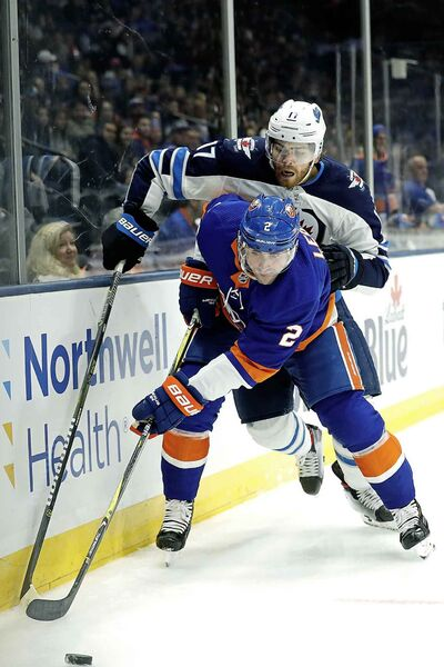 New York Islanders defenseman Nick Leddy (2) and Winnipeg Jets center Adam Lowry (17) reach for the puck during the first period Sunday, Oct. 6, 2019, in Uniondale, N.Y. (Michael Owens / The Associated Press)