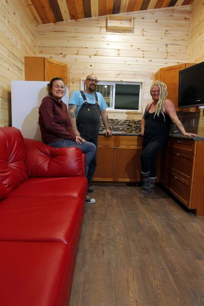 BORIS MINKEVICH / WINNIPEG FREE PRESS</p><p>Anita Munn (right) her husband, Darrell Manuliak (centre) and daughter Bridget Stewart pose for a photo in one of a mini homes they will deliver this week to a client near Clear Lake.</p>