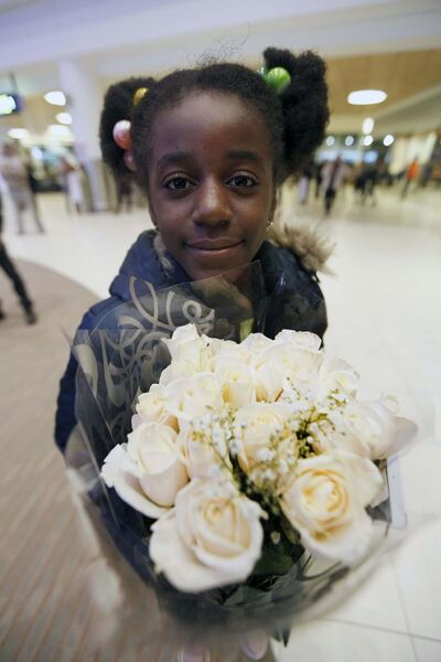PHIL HOSSACK / WINNIPEG FREE PRESS</p><p>Rachael Bisimwa, 9, waits patiently, holding a bouquet of white roses, to welcome her sister Naomi.</p>