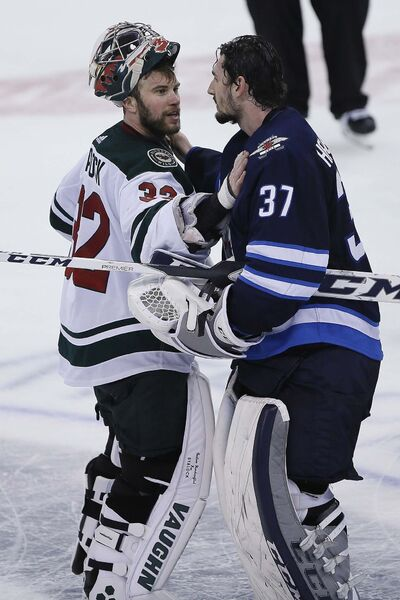 Minnesota Wild's goaltender Alex Stalock (32) congratulates Winnipeg Jets goaltender Connor Hellebuyck (37) after the Wild were defeated in game five NHL playoff action in Winnipeg on Friday, April 20, 2018. THE CANADIAN PRESS/John Woods</p>