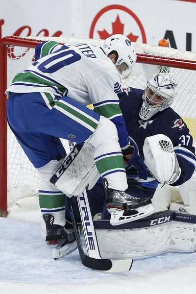 JOHN WOODS / THE CANADIAN PRESS</p><p>Canucks forward Brandon Sutter barges into Jets goalie Connor Hellebuyck's crease. Hellebuyck is starting to find his form this season.</p></p>