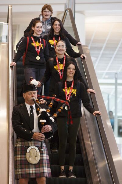 MIKE DEAL / WINNIPEG FREE PRESS</p><p>Members of Team Manitoba lead by skip Kerri Einarson (foreground), Shannon Birchard (middle), Briane Meilleur (back left) and Jennifer Clark-Rouire (back right), are piped in on their arrival back home Monday morning.</p>