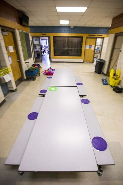 Colourful discs are affixed to lunch tables to give kids space during meals, and tape is being used to create distance markers indoors and out. (Mikaela MacKenzie / Winnipeg Free Press)