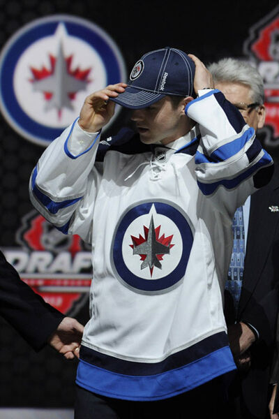 Joshua Morrissey, a defenceman, adjusts a Winnipeg Jets hat after being chosen 13th overall in the first round of the NHL hockey draft, Sunday, in Newark, N.J.