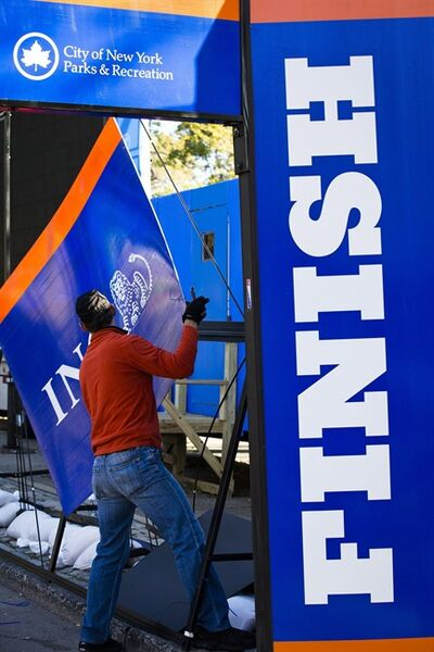 FILE - In this Nov. 3, 2012 file photo, a worker dismantles sponsorship signs at the Central Park finish line for the canceled New York Marathon in New York. The increased security will be unmistakable for the Nov. 3, 2013, marathon, from barriers around Central Park to added checkpoints. (AP Photo/ John Minchillo, File)