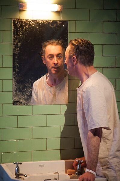 "This undated theater image released by National Theatre of Scotland shows Alan Cumming in ""Macbeth."" In the play, Cumming appears as a patient in a white-tiled mental hospital for whom the plot of ""Macbeth is sort of a schizophrenic nightmare. Producers said Friday that the Tony Award winning Scottish actor will bring his one-man ""Macbeth to Broadway's Ethel Barrymore Theatre beginning April 7. It will run through June 30. (AP Photo/National Theatre of Scotland, Manuel Harlan)"