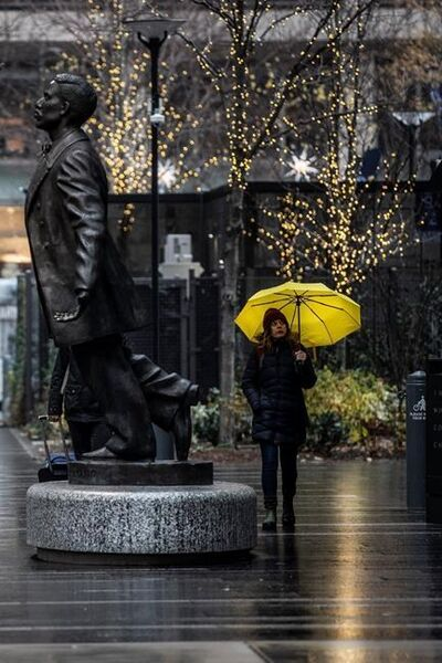 An unidentified woman shields from the rain with an umbrella as she walks near the Octavius Catto statue, Sunday, Dec. 1, 2019 in Philadelphia. (Jose F. Moreno/The Philadelphia Inquirer via AP)