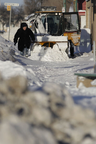 A pedestrian makes her way around a stalled snow blower on Main Street Sunday.