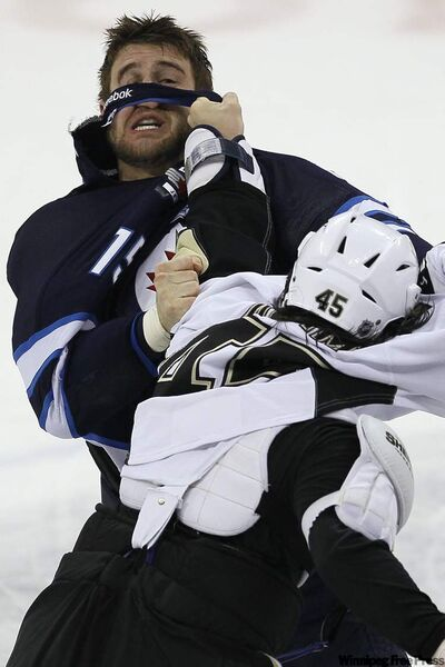 Winnipeg Jets forward Tanner Glass (15) and Pittsburgh Penguins' forward Arron Asham (45) fight during first-period NHL action in Winnipeg on Friday.