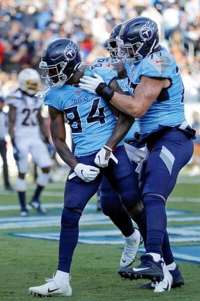 Tennessee Titans wide receiver Corey Davis (84) celebrates with offensive tackle Taylor Lewan (77) after Davis scored a touchdown against the Los Angeles Chargers in the first half of an NFL football game Sunday, Oct. 20, 2019, in Nashville, Tenn. (AP Photo/James Kenney)