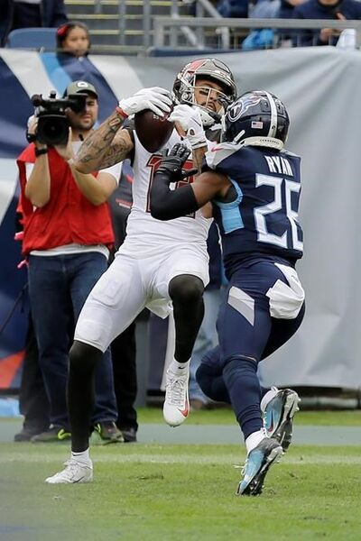 Tampa Bay Buccaneers wide receiver Mike Evans, left, scores a touchdown against Tennessee Titans cornerback Logan Ryan (26) on a 2-yard pass play in the second half of an NFL football game Sunday, Oct. 27, 2019, in Nashville, Tenn.(AP Photo/James Kenney)