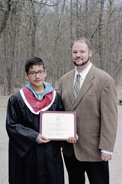 """Winnipeg student Sterling Flett received a $1,000 RESP given to the winner of the """"I Will Succeed Award"""" from program manager Lee Foster at Career Trek's Children Rising graduations ceremony at Camp Manitou on April 24."""